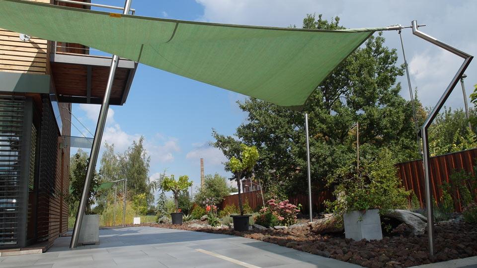 Ein grünes Sonnensegel über einer Hauseinfahrt