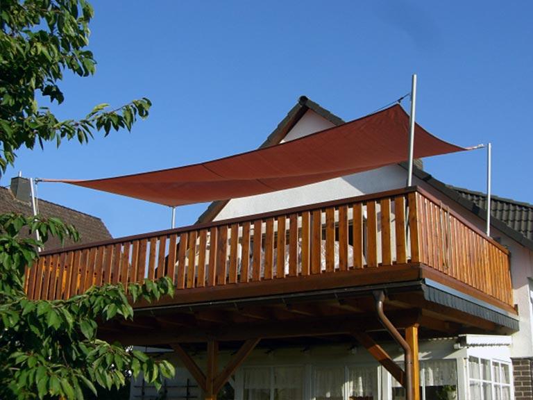 Ein rotes Sonnensegel installiert auf einem Balkon