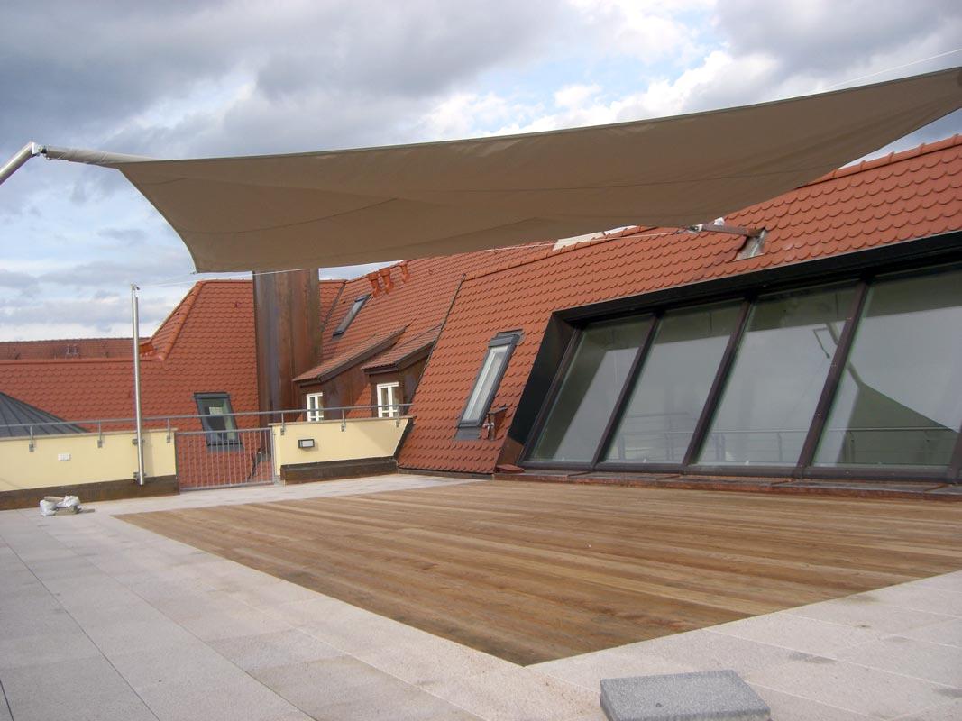 Ein aufrollbares Sonnensegelsystem auf einer Dachterrasse mit Holzdielen