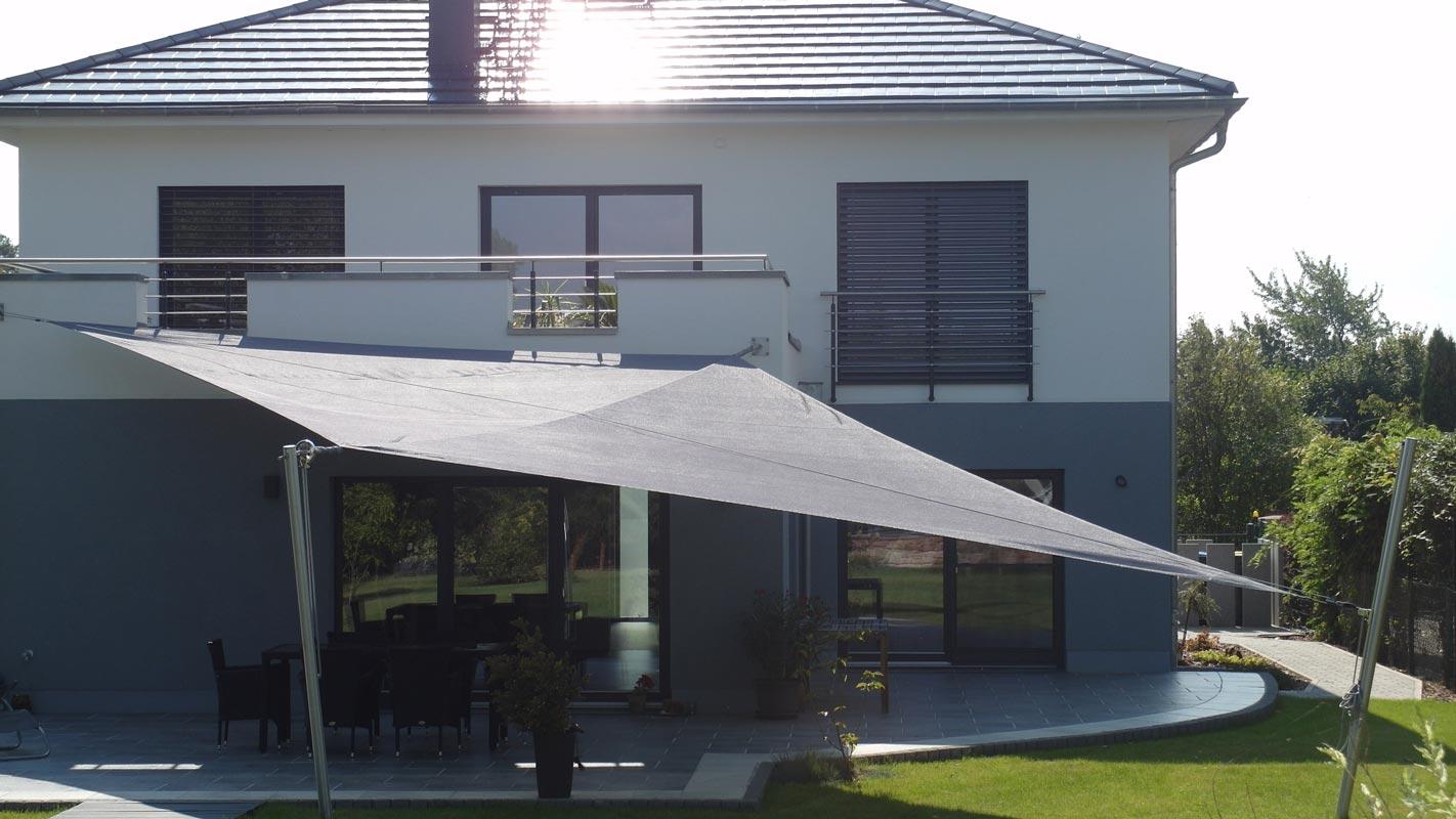 Ein an einem Wohnhaus installiertes aufrollbares Sonnensegel