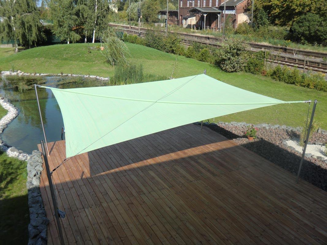 Grünes Sonnensegel über einer Terrasse an einem Teich