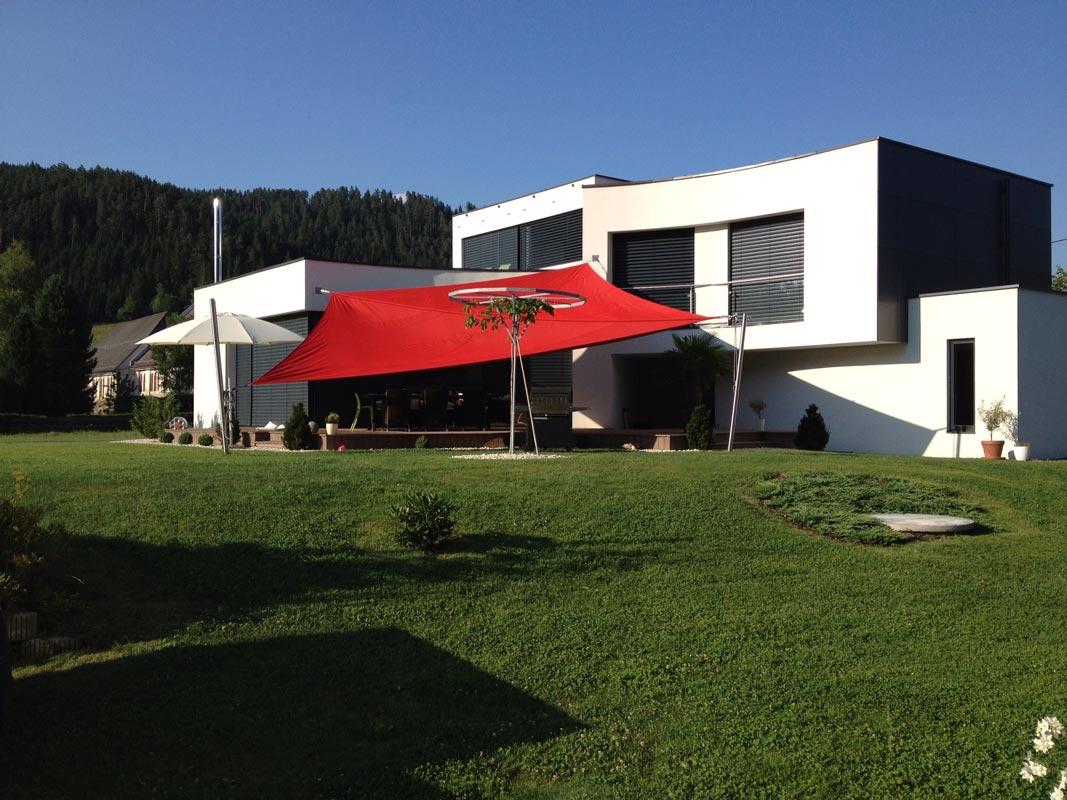 Ein rotes aufrollbares Sonnensegel an einem modernen Wohnhaus