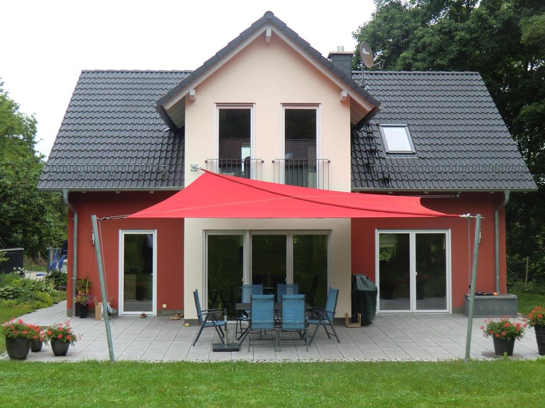 Ein rotes aufrollbares Sonnensegel über einer Terrasse mit Tisch und Stühlen