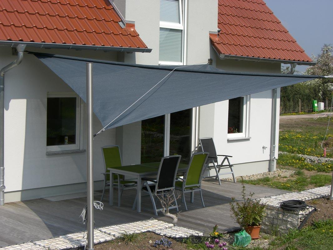 Ein aufrollbares Sonnensegel hinter einem Haus mit Terrasse