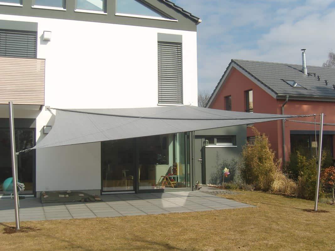 Ein graues Sonnensegel hinter einem Wohnhaus