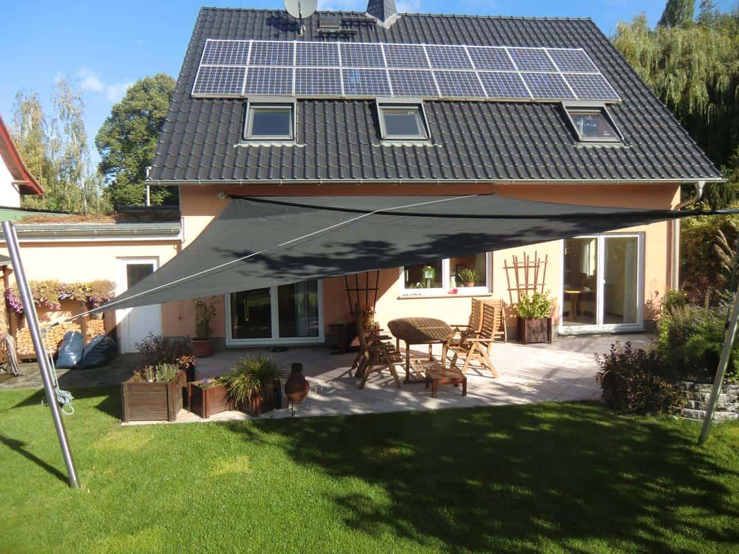 Ein Wohnhaus mit aufrollbarem Sonnensegel über der Terrasse