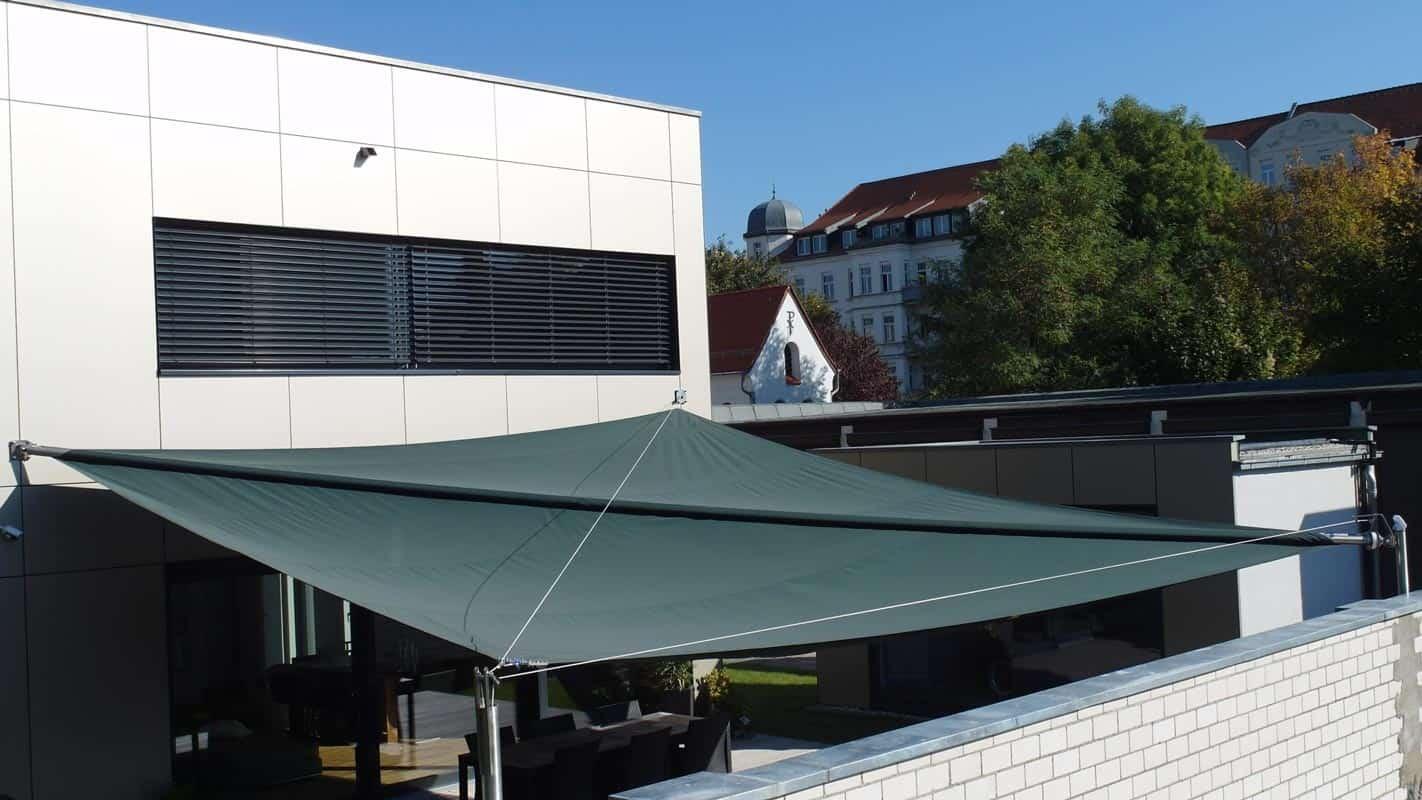 Ein automatisch aufrollbares Sonnensegel über einem Innenhof