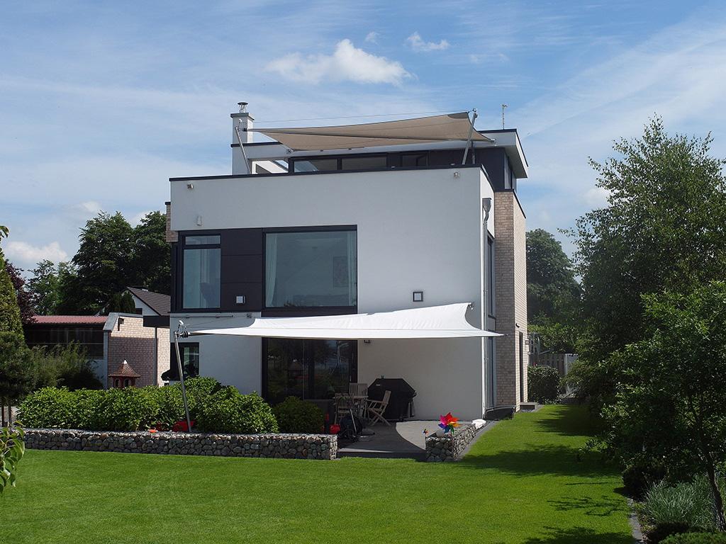 Weißes automatisches Sonnensegel an einem Haus