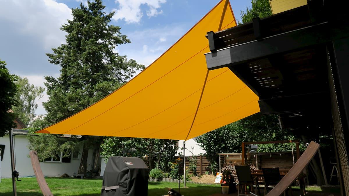 Gelbes Sonnensegel in einer Gartenanlage