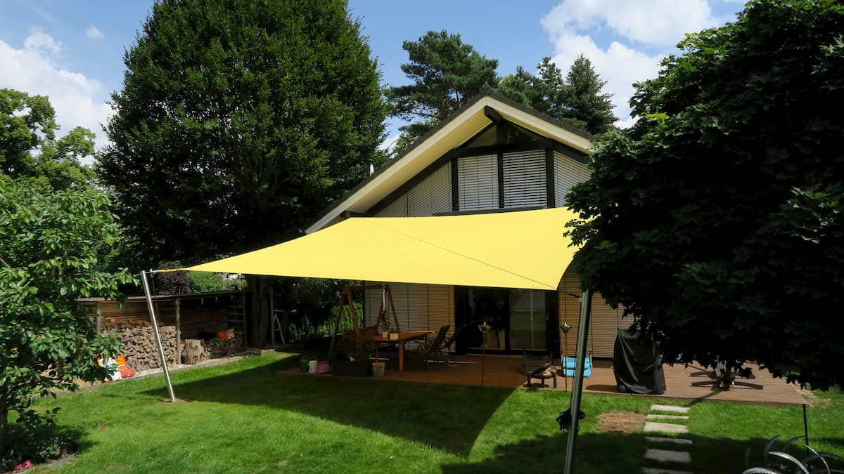 Gelbes Sonnensegel über einer Terrasse in einem Garten