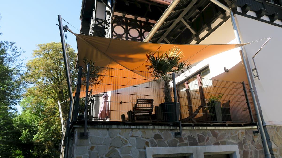 Oranges Sonnensegel beschattet kleinen Balkon