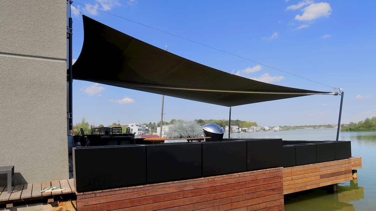 Schwarzes Sonnensegel über einer Terrasse am Wasser