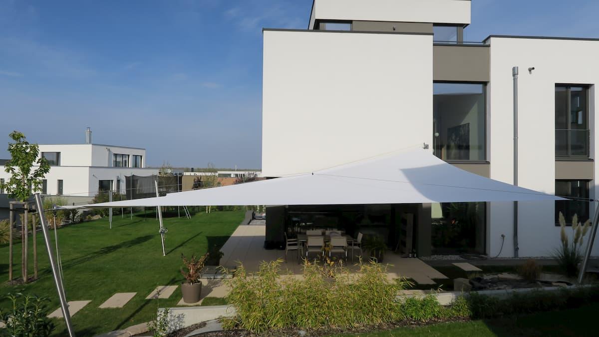 Großes Sonnensegel über Terrasse an Gartenanlage