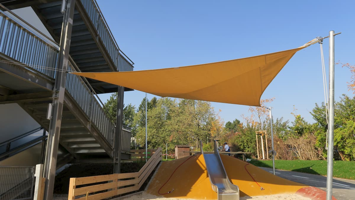 Gelbes Sonnensegel über Kinderspielplatz