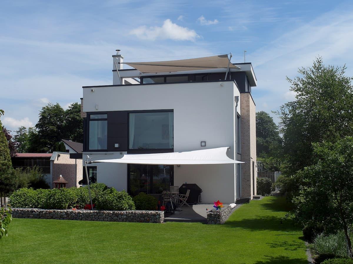 Weißes Sonnensegel für große Terrasse an Garten