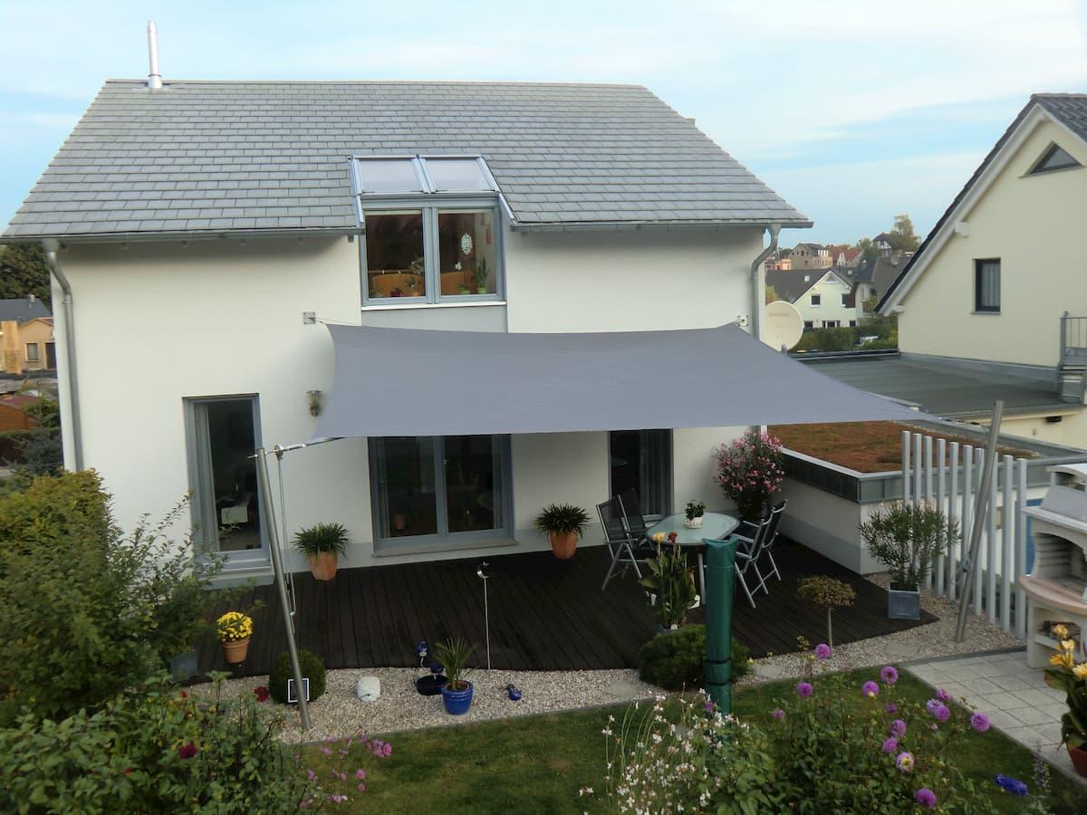 Graues Sonnensegel an Wohnhaus-Terrasse